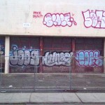 The chain-link fence surrounding the toxic site did little to deter local taggers.  Every morning, the OUSD auto shop at 1032 4th Avenue seemed more colorful than it had been the night before. (Tagged for Demolition.  Edward Cervantes, Oakland Voices, 2012)
