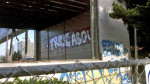 """Sprayed on the shell of a toxic school site, the """"stay in school"""" cliché is given an amusing twist. (Irony: Stay in School.  Edward Cervantes, Oakland Voices 2012)"""
