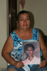 Central American mother holding a picture of her missing son