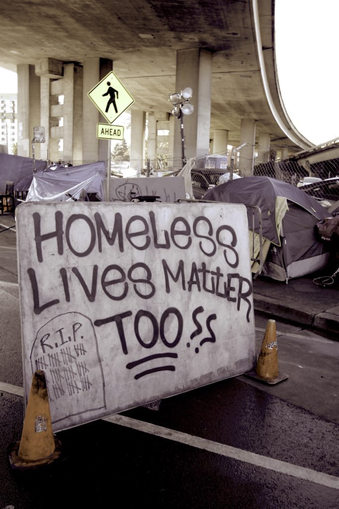 "A large ""Homeless Lives Matter??"" sign camp residents built to shield themselves from traffic."