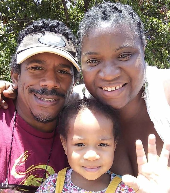 An African American family (man, woman, and toddler) smile at the camera in a selfie photo.